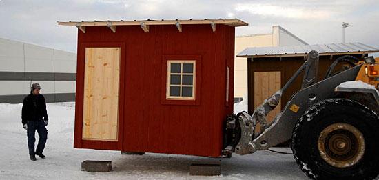 En rødmalt hytte fraktes ut fra fabrikken med gaffeltruck for å bli solgt som