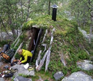 Skarpholet i Femundmarka er ei lita jordgamme som går helt i ett med omgivelsene. Hilde sitter i døråpninga og lager dagens middag.