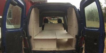 Innredning med sitte- og soveplass for to voksne personer, pluss skap med luker på hver side.