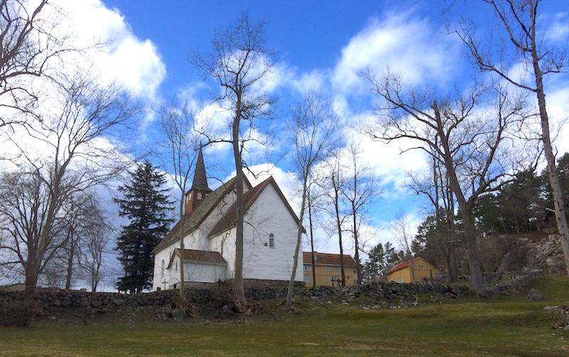 Veøya kirke med prestegarden i bakgrunnen.